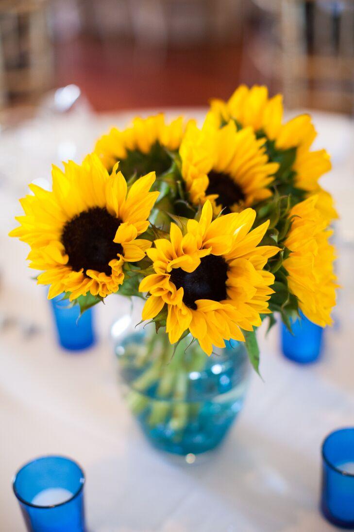 Bright yellow sunflower centerpieces in aqua blue vases