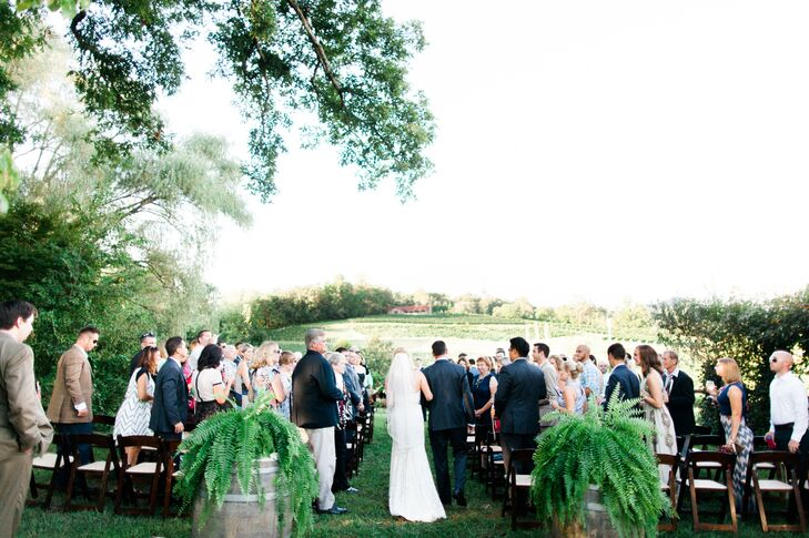 """We chose to keep the ceremony decor in line withrnthe theme with the vineyard itself,"" says Cory. ""It's an eclectic place so we chose to have lots of ferns, candles, wooden accents and flowers."""