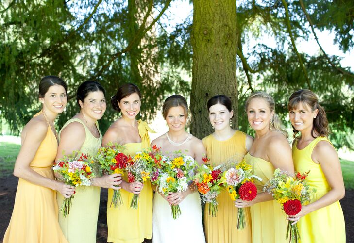 The bride stood with her bridesmaids dressed in a variety of yellow dresses, each holding a colorful bouquet of flowers.