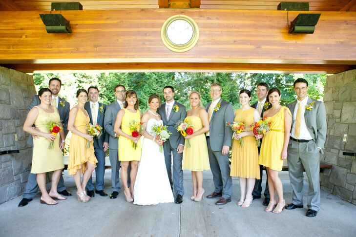 The bride and groom stood with their wedding party, who were dressed in gray or yellow attire.