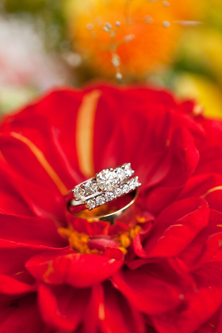 The engagement ring, wedding ring and wedding band were displayed on top of a bright red flower.