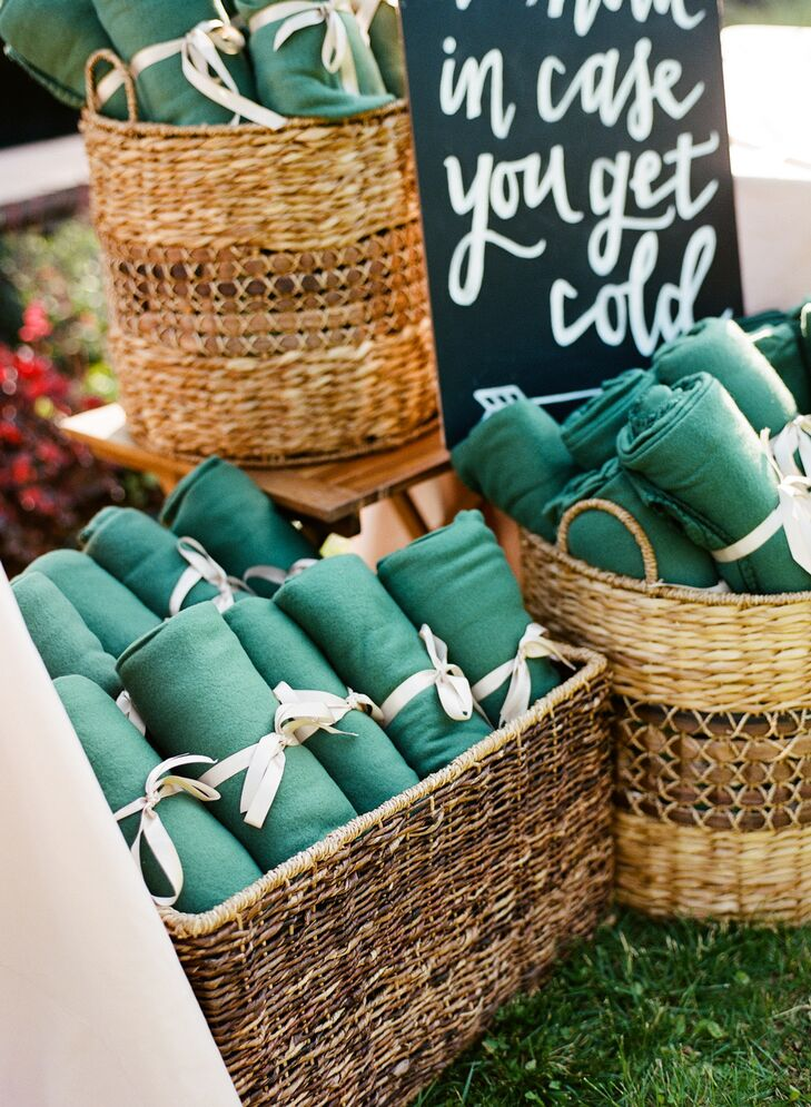 """Jamie and Alex wanted guests to stay warm during their ocean-side celebration, so they provided blankets wrapped with satin ribbon. They were displayed in baskets with a cheeky hand-painted sign that read """"To have and to hold, in case you get cold."""""""