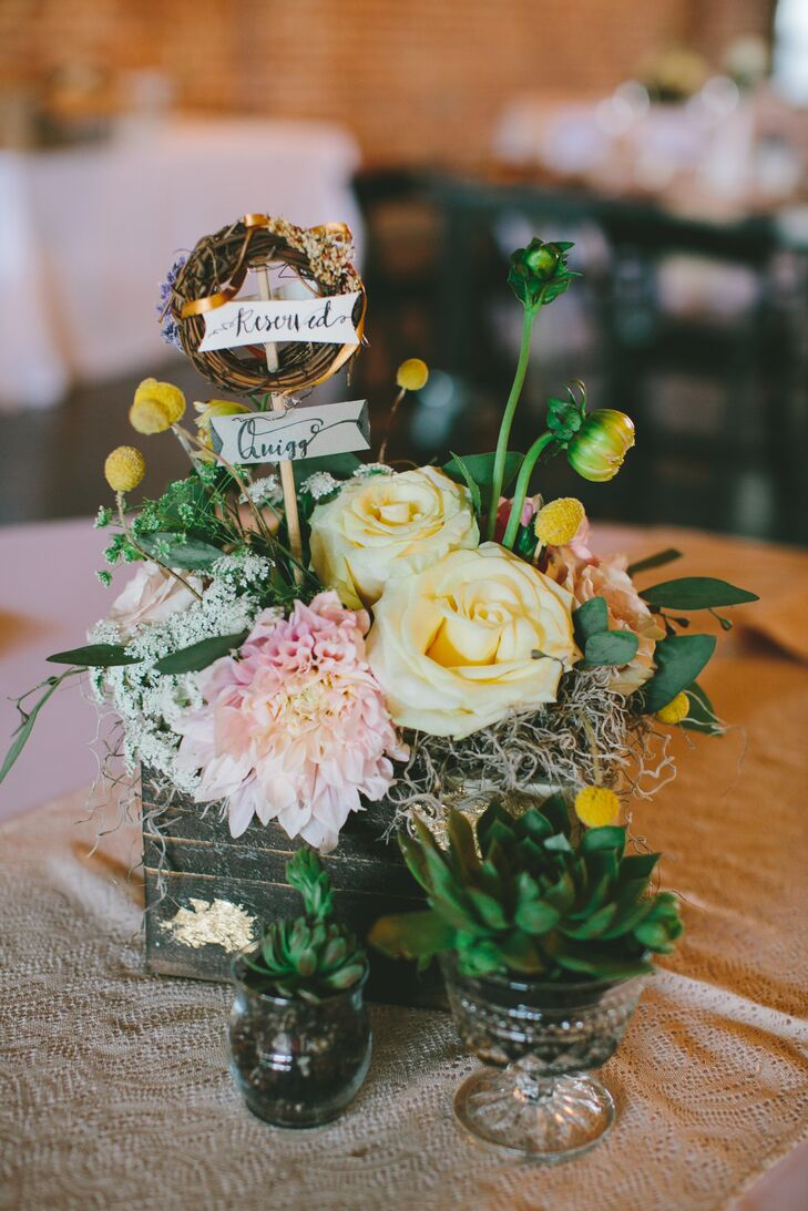 Poppy and Clover designed several centerpieces for the reception, ranging from milk glass vases filled with white full blooms to quirky wooden slices topped with brass antiques. Other tables were decorated with bunches of roses, dahlias and a mix of dried moss, mums, scabiosas and greenery arranged in rustic wooden boxes. Lush, green succulents completed the display, each one placed in decorative vintage glass.