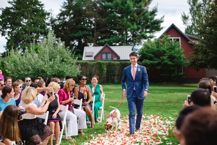 Hannah and Ed's faithful pup made an appearance during the ceremony, much to the delight of guests, joining Ed as he made his way down the rose-petal-adorned aisle. Keeping with the wedding's color scheme, their canine companion sported a coral leash and harness.