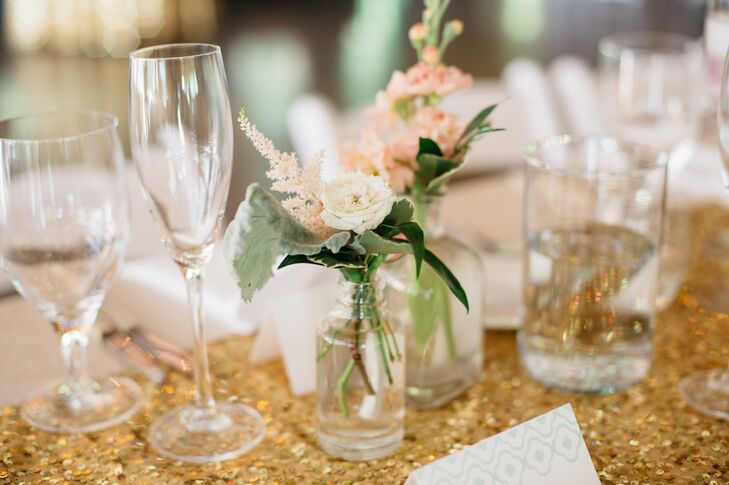 The wedding's color palette was predominately mint and gold, and Katharine and Nate used flowers to add pink to the decor. For the reception, the pair dotted the glam tablecloths with bud vases with an assortment of seasonal blooms in soft blush and playful pink.