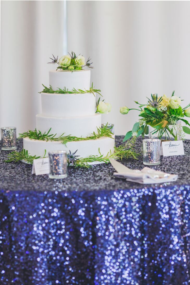 The four-tier buttercream cake was wrapped in a greenery garland and featured two flavors: lemon berry and chocolate raspberry.