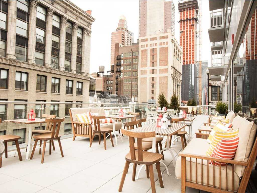 View of Mondrian Terrace outdoor deck with rustic furniture and surrounding buildings
