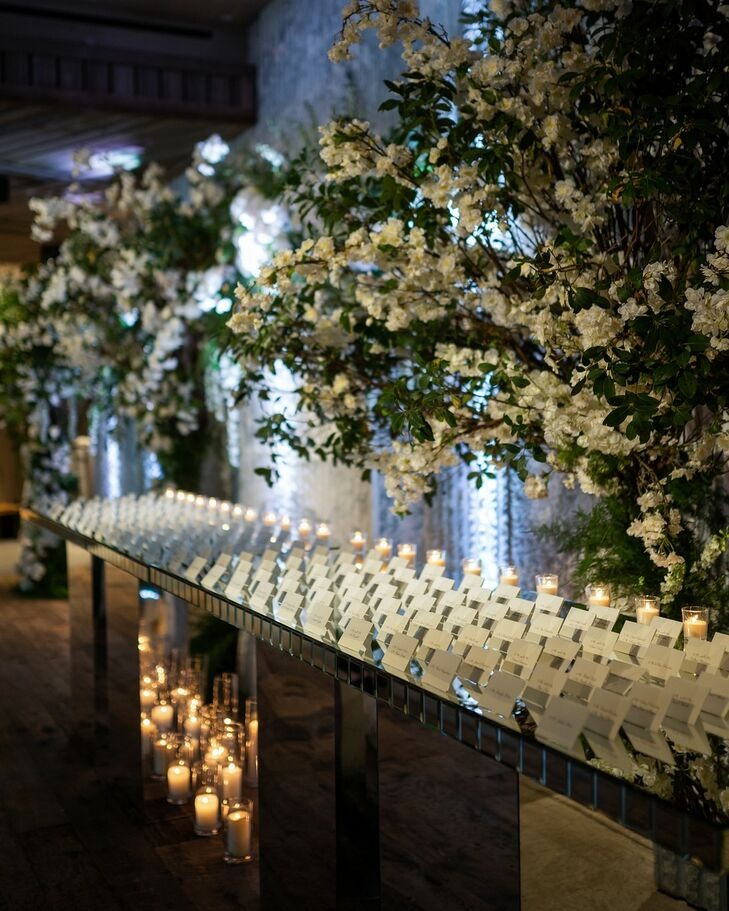 Elegant Escort Card Display with Candles and Flower Arrangements