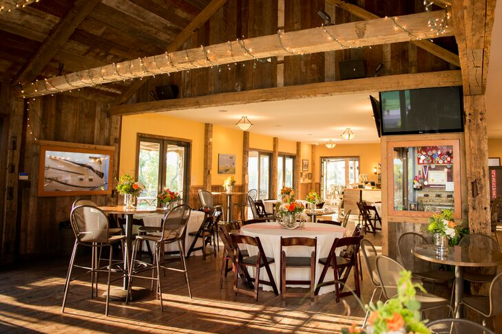 The wood beams at the barn reception were decorated with fairy lights, and the round dining table featured white and orange centerpieces.