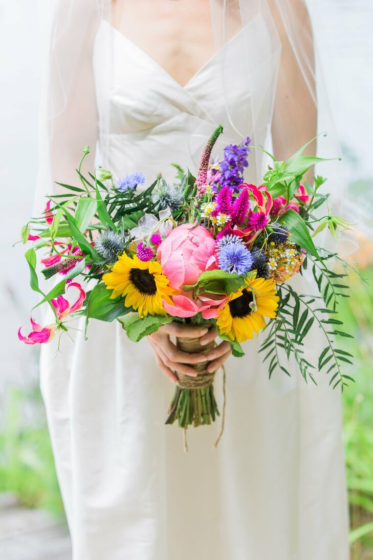 Drawing on the couple's rustic, backyard theme for inspiration, the florists at Lotus Floral Design created a textured arrangement of wildflowers, sunflowers and peonies in vibrant shades of yellow, purple, blue and pink for Liz to carry down the aisle.