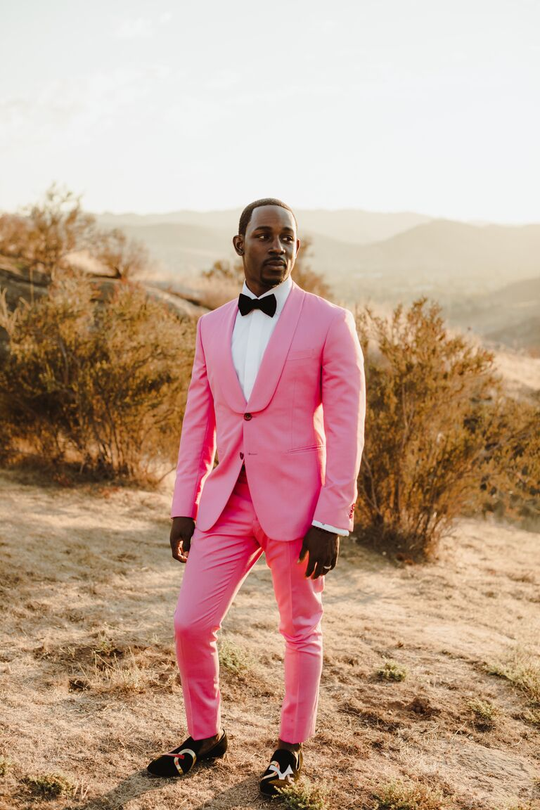 Black groom standing outside wearing hot pink suit and bowtie matching 2021 wedding colors