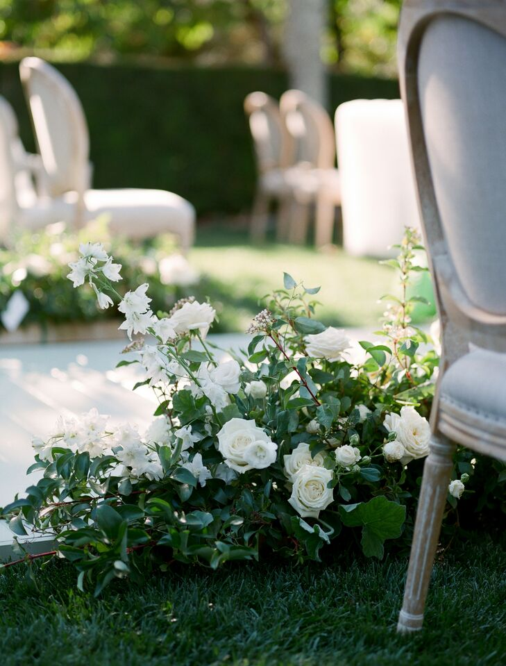 White Flower Arrangements With Greenery Lining the Ceremony Aisle