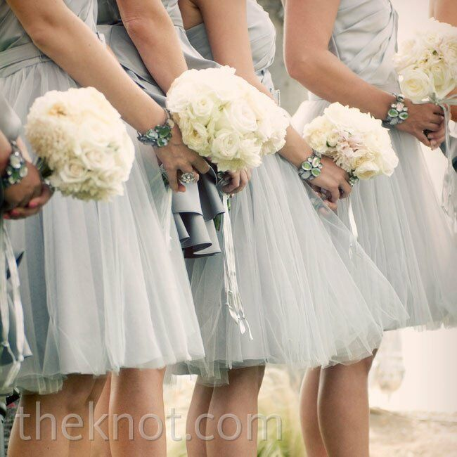 Lush all-white bridesmaid bouquets tied with silver ribbon fit with the classic-meets-glam look of the day.