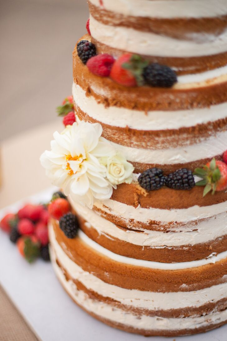 The naturalistic, rough-frosted wedding cake from Krumbs Bakery in San Rafael, California, was topped with fresh blossoms and berries.