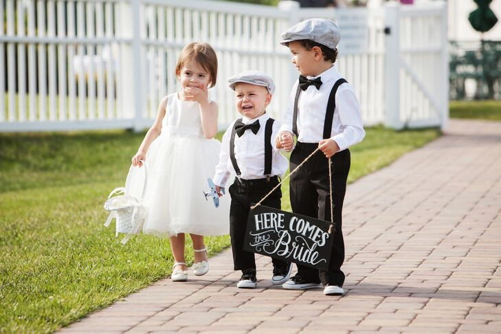 """Rachel and Dave's nephews served as their ring bearers, walking down the aisle wearing formal, vintage-inspired ensembles. Matching the groomsmen suits, the boys donned black trousers, crisp white button-downs, black bow ties and suspenders, which they paired with Converse sneakers and gray flat caps. The older of their two nephews carried a hand-lettered chalkboard sign that said """"Here comes the bride,"""" while their younger nephew carried a toy airplane. """"The airplane wasn't panned, but was used as an attempt to keep him from crying,"""" Rachel says."""