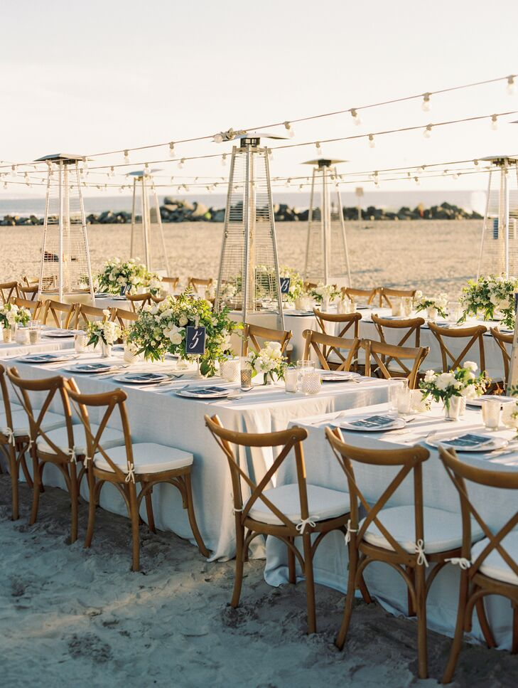 At the seaside reception, long banquet tables were topped with simple pale blue linens and illuminated by string lights after the sun went down.