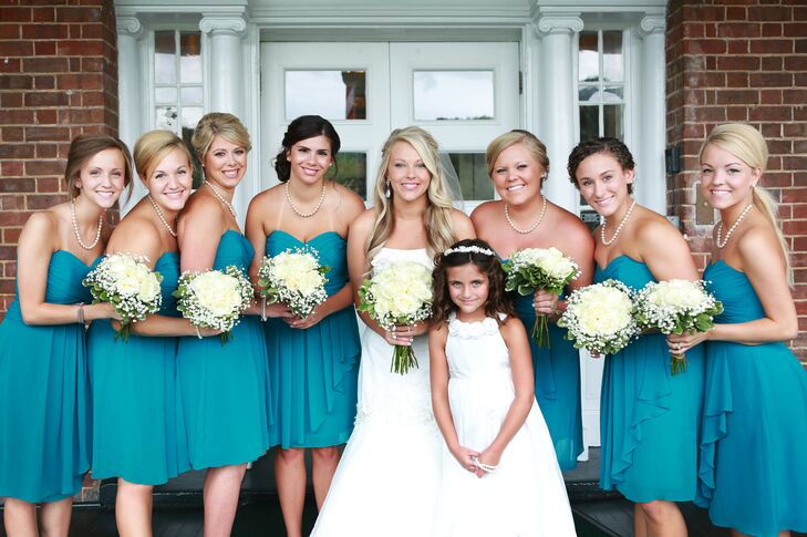 Molly's bridesmaids wore strapless, knee-length dresses in teal. They styled their hair up and wore matching pearl necklaces.