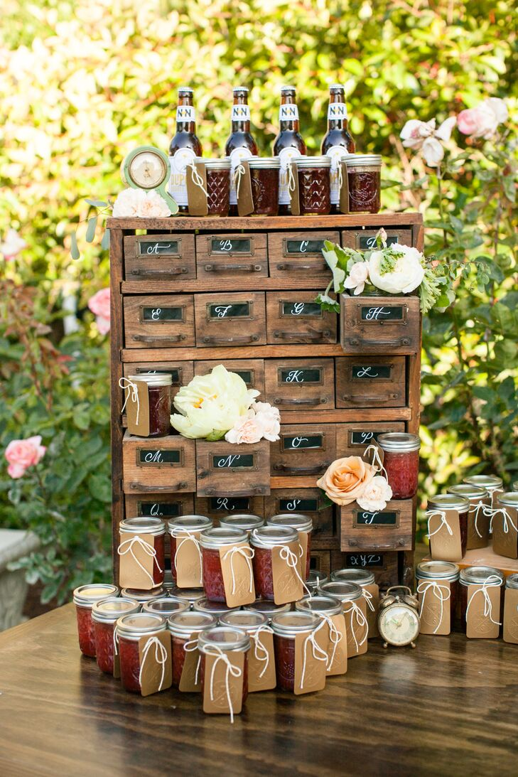 At the reception, stacks of freshly made jams were displayed for guests to take home, with tags attached to each jar that had the couple's personalized logo on them. Behind the jar arrangement was a tall wooden piece decorated with flowers, and on top were home-brewed bottles of beer that were given out as wedding favors as well.