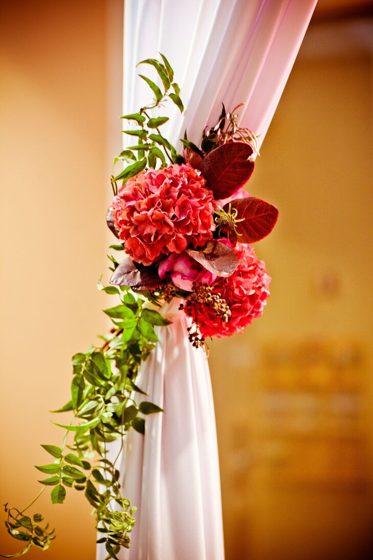 Small blooms of pink hydrangeas were tied to the white ceremony draping.