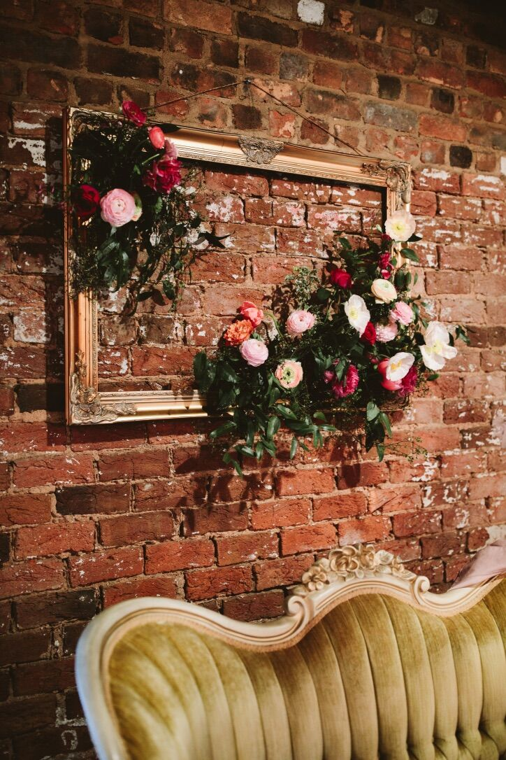 Elegant Wood Frame and Flower Arrangements on Brick Wall