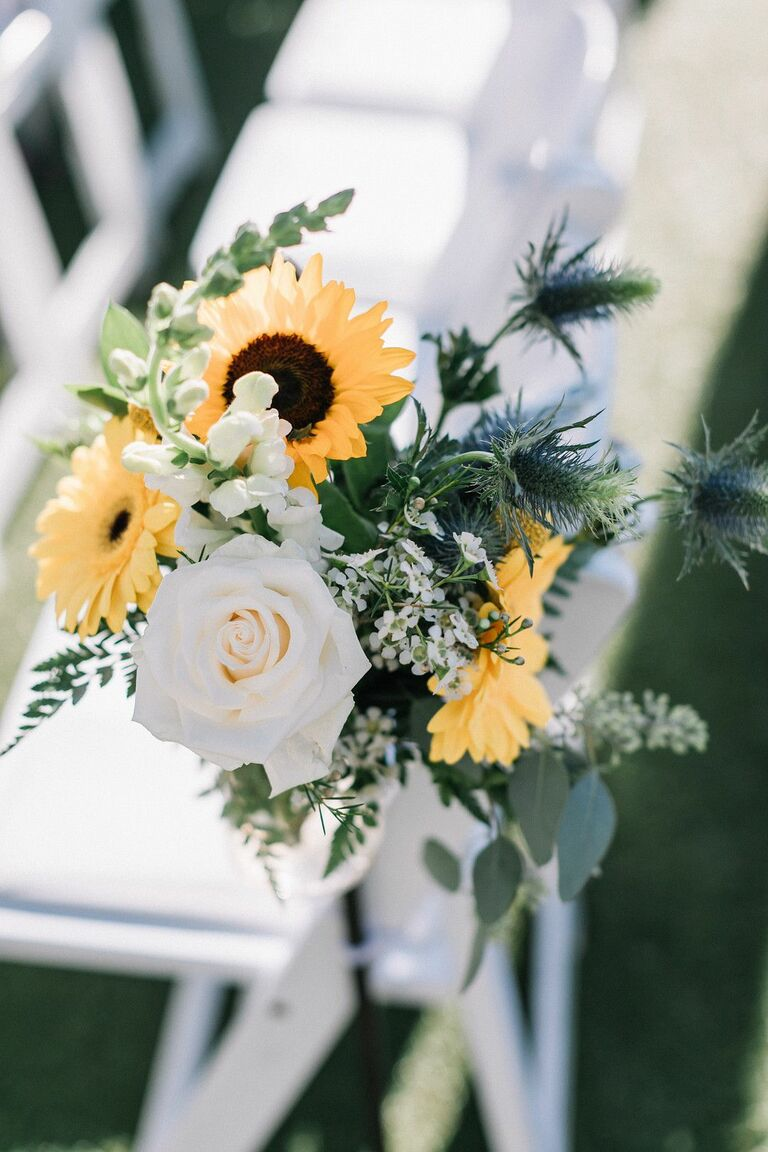 Ceremony aisle markers with thistles, white roses and sunflowers