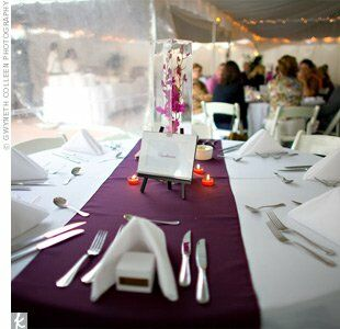 A plum table runner and orange tea light candles set the canvas for the centerpiece that Kate and Chris designed themselves. Purple orchids submerged in tall vases provided dramatic focal points for the tables, each named for one of the couple's favorite movies.