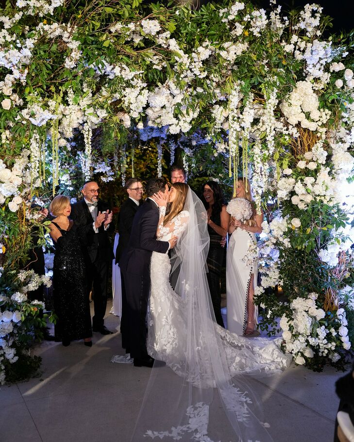 Elegant First Kiss and Chuppah with White Flowers and Greenery
