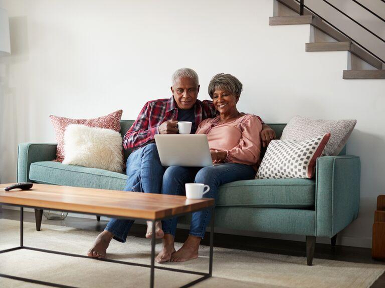 Couple sitting on sofa watching something on their laptop