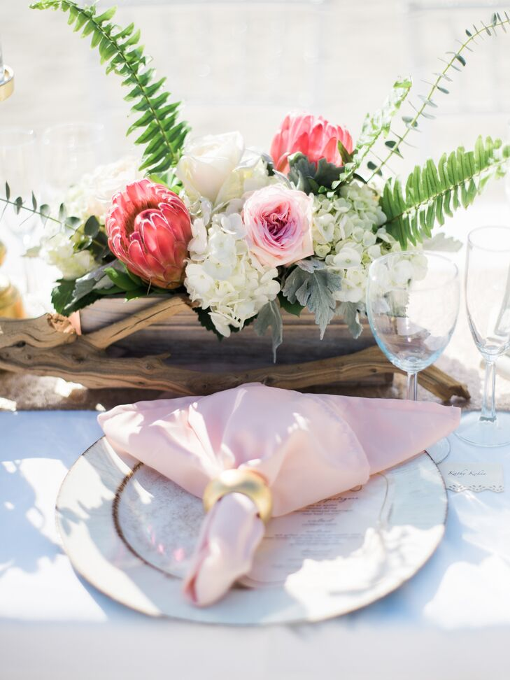"""""""I had menus printed that matched my invitations, which sat at each place setting. The florist worked her magic with wooden boxes filled with beautiful flowers and gold candle pillars,"""" Nicole says."""