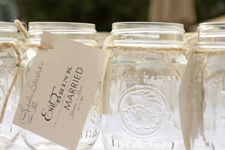 "Mason jars doubled as escort cards at the Southern-inspired rustic wedding. Terri made the black-and-white ""Eat, Drink and Be Married"" tags herself for the cards. Guests enjoyed sweet tea, lemonade and Arnold Palmers out of the mason jars with the chicken and waffles and shrimp and grits menu."