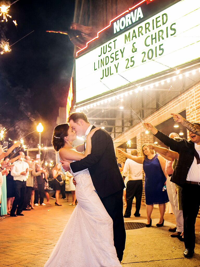 Bride and groom sparkler exit and kiss outside a theater