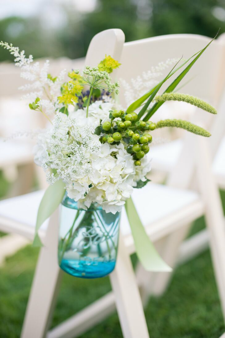 A few mason jars filled with flowers hung on the back of the aisle chairs.