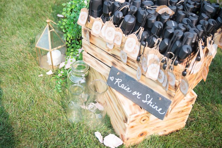 A wooden box filled with umbrellas was made available to guests for the outdoor ceremony in case it started to rain.