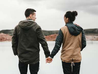 couple holding hands outdoors facing away from the camera