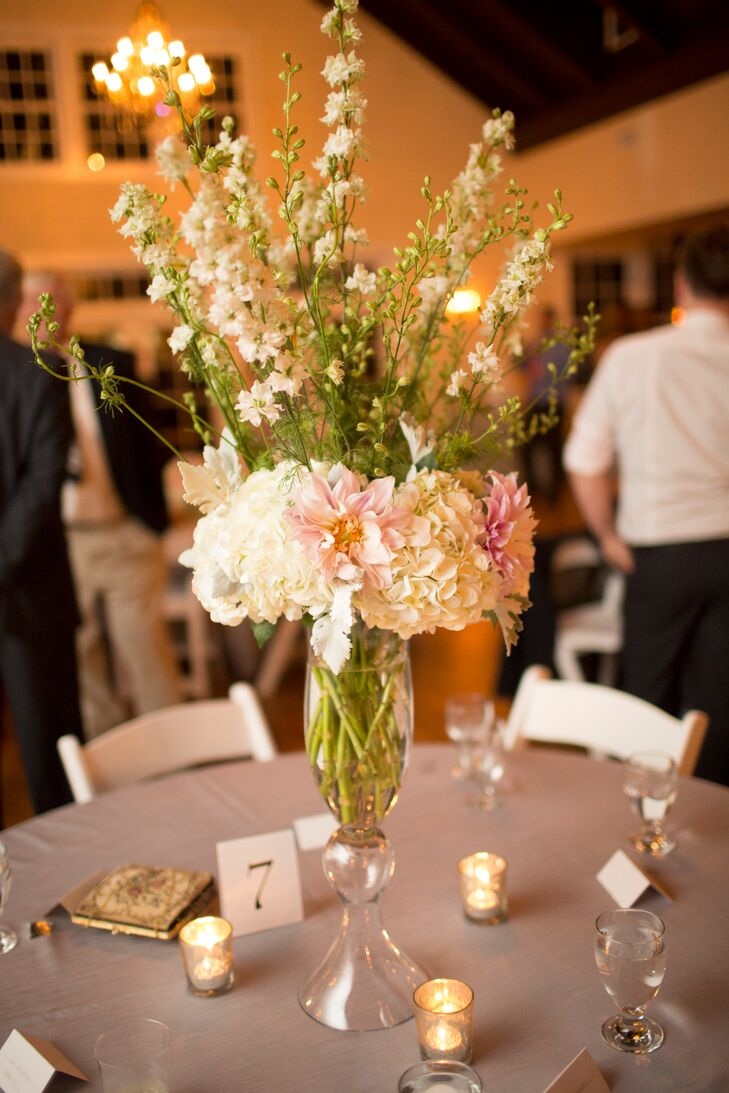 Centerpieces at the Portsmouth wedding included white hydrangeas, light pink dahlias and white delphiniums with sprigs of dusty miller in glass trumpet vases.