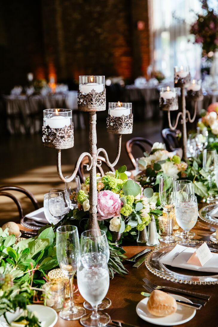 The floral arrangements were key to a romantic, feminine feel in the vast space; iron candelabras also combined romance and rusticity.