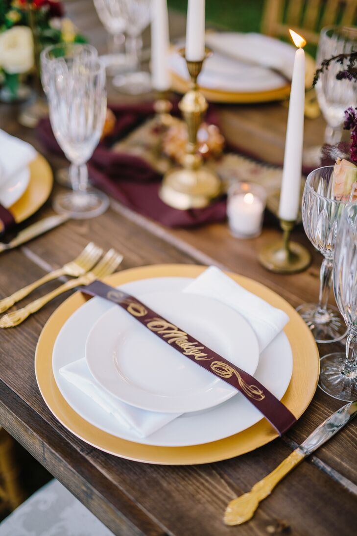 A deep purple leather escort card tucked around each place setting, calligraphed in gold by Myrtle and Lloyd. The dinnerware included a white plate anchored by a gold charger, with gold flatware that stood out from the rustic wooden farm table.