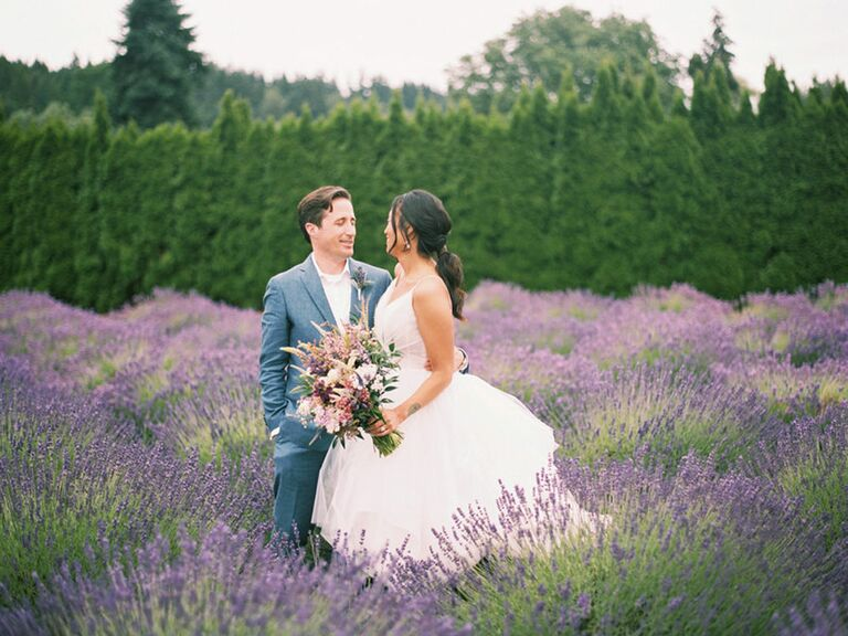 Bride and groom in lavender field with bouquet of purple wedding flowers