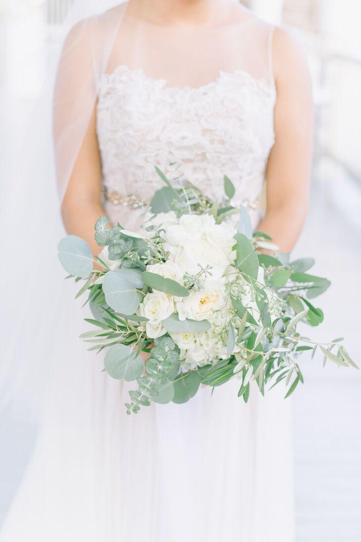"""""""I limited the floral arrangements to white flowers to keep it simple and clean,"""" Jennifer says. """"I think the florals brought a freshness and lightness to the event."""" Jennifer's bouquet incorporated soft white blooms and eucalyptus."""