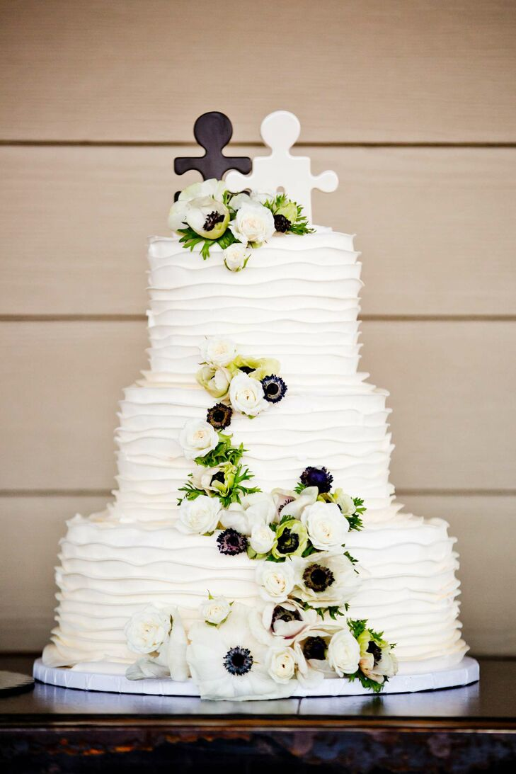 The cake was a chocolate cake with Bavarian creme and marble cake with fudge filling on the inside. The outside was decorated with cream cheese frosting and cascading anemones. The black-and-white puzzle piece cake toppers were actually salt and pepper shakers, which Taylor and Jehre now use in their home.