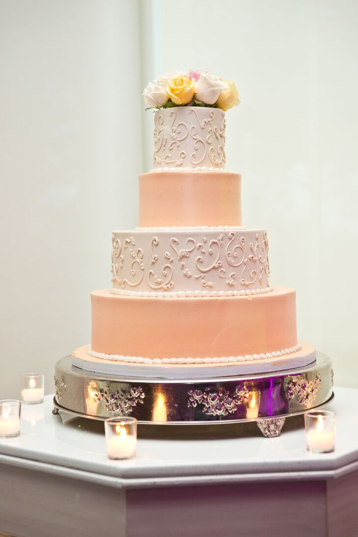 The four tier wedding cake had alternating fondant layers of white and peach frosting.