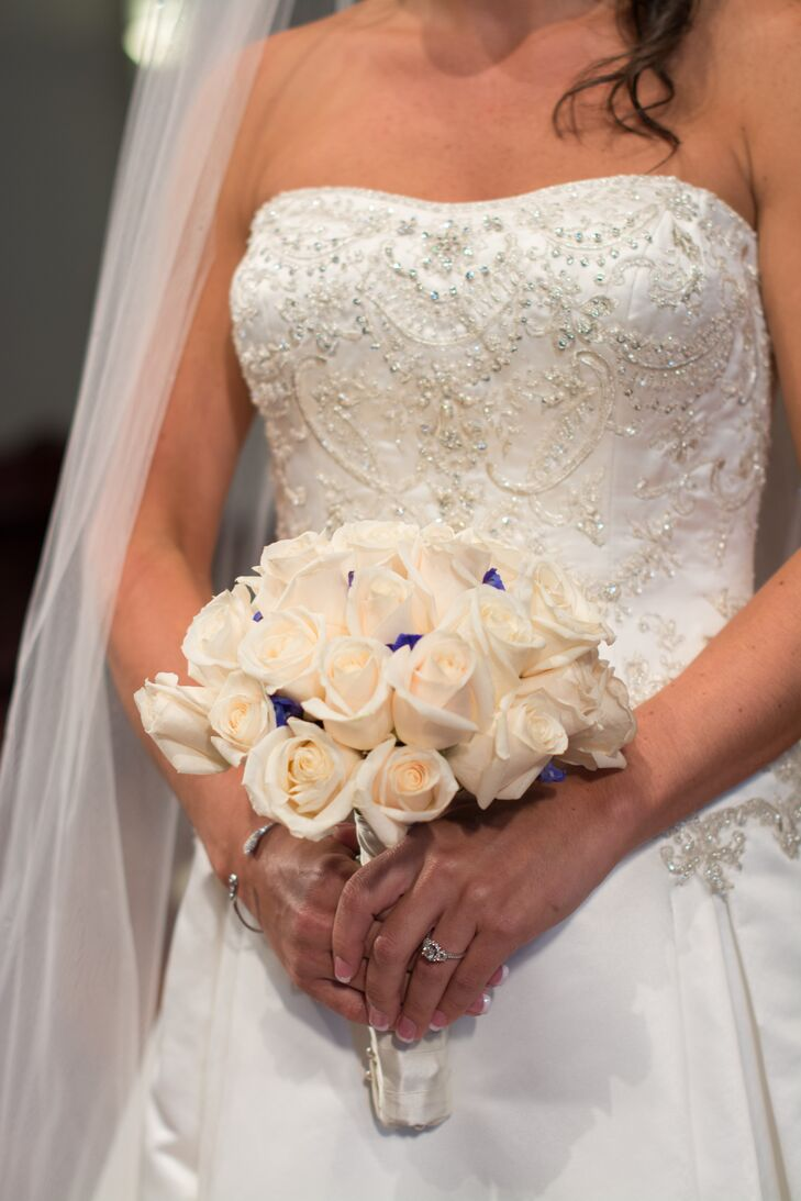 Pops of electric blue delphiniums added color to the bride's white rose wedding bouquet. rn
