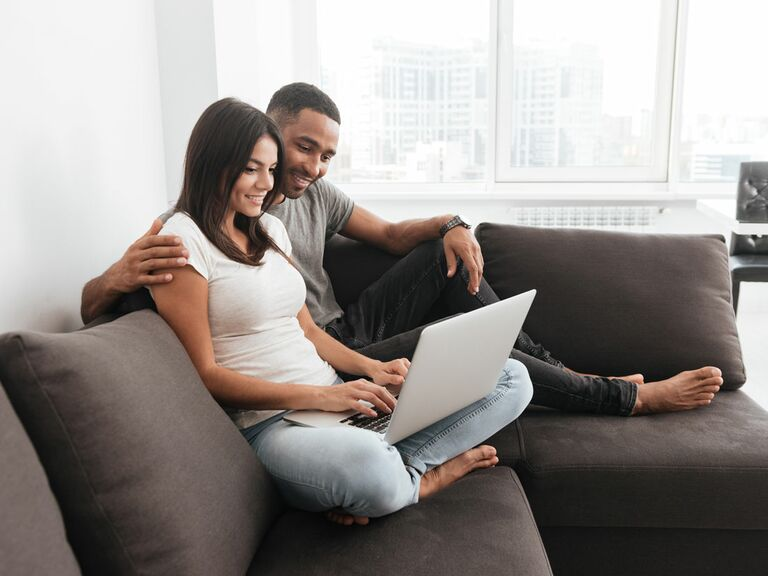 Engaged couple using laptop at home