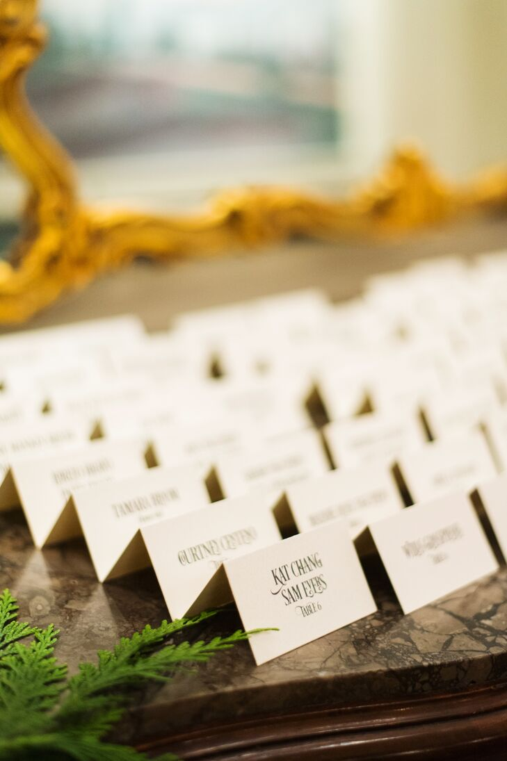 Though the couple didn't have a specific theme at the beginning of the planning process, a distinct 1920s vibe developed organically out of each decision. The escort cards took on a subtle art deco tone with fanciful script that brought the classic white cards to life.