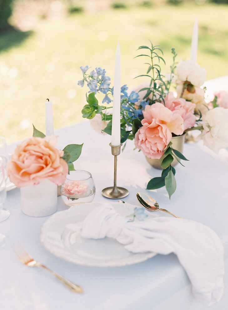 At the reception's ivory linen-topped tables, gold candlesticks sat among peach and blue floral blossoms.