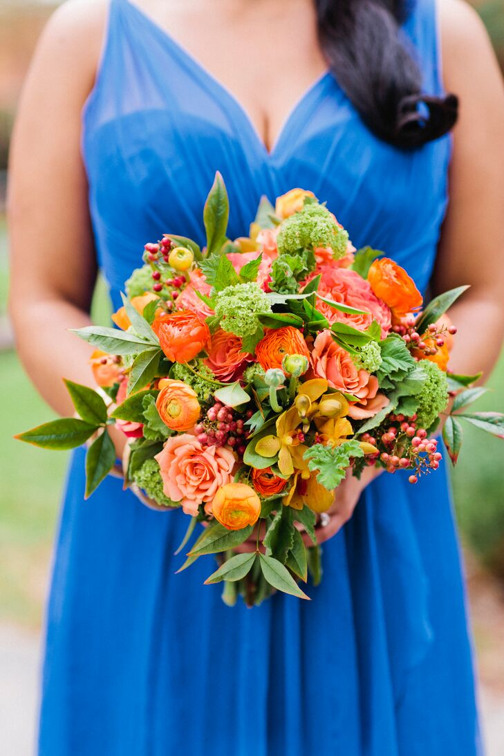 Amanda's two bridesmaids donned vibrant cobalt blue gowns and carried a bouquet of cheery orange blooms.