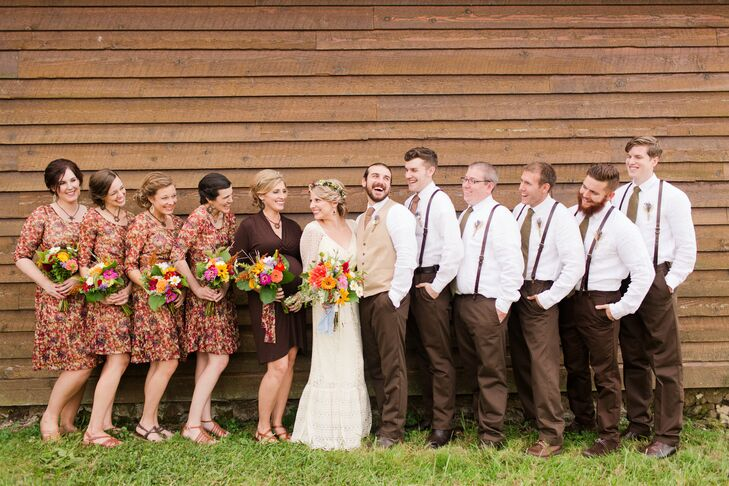 Carlyn and Ben posed with their wedding party in front of a wooden backdrop, which matched the day's natural-colored attire. The groomsmen sported brown suspenders that Ben found on Etsy, attached to a pair of brown pants. The bridesmaids wore matching knee-length floral dresses in several colors with their brown sandals.