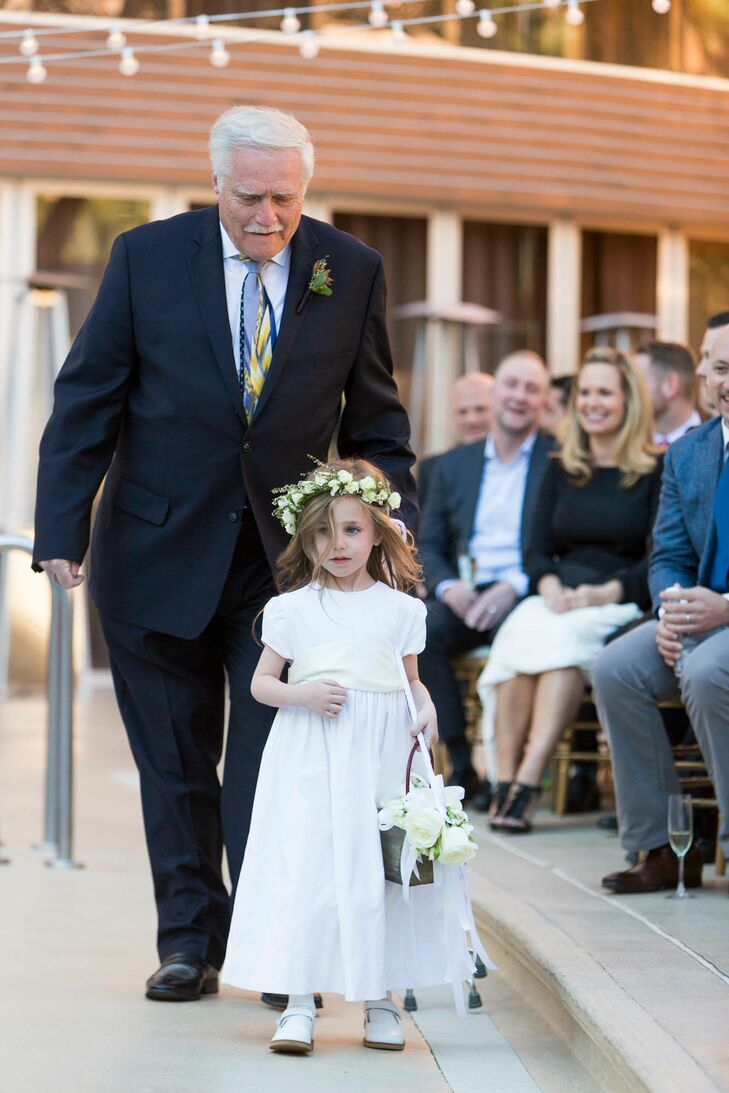 The fathers of the grooms escorted the children down the aisle. Both wore white attire from Bailey Boys Classic Collection in contrast to their fathers' dark suits.