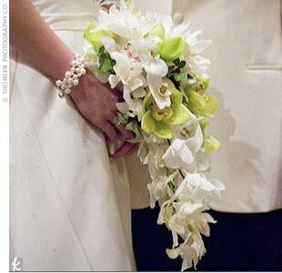 Feathers were incorporated throughout the attire and decor to enhance the retro look of the celebration. While her bridesmaids' bouquets had feather collars, Tracie carried a cascading bouquet of white phalaenopsis and green cymbidium orchids.