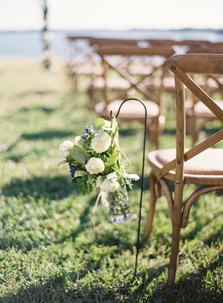 The waterfront ceremony was decorated with mason jars overflowing with garden flowers and rustic wooden chairs.